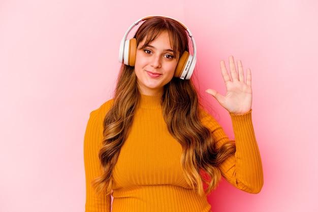 손가락으로 명랑 보여주는 번호 5를 웃고 고립 된 헤드폰으로 젊은 여자 듣기 음악