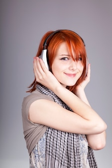 Young woman listening music with headphones. portrait on grey background