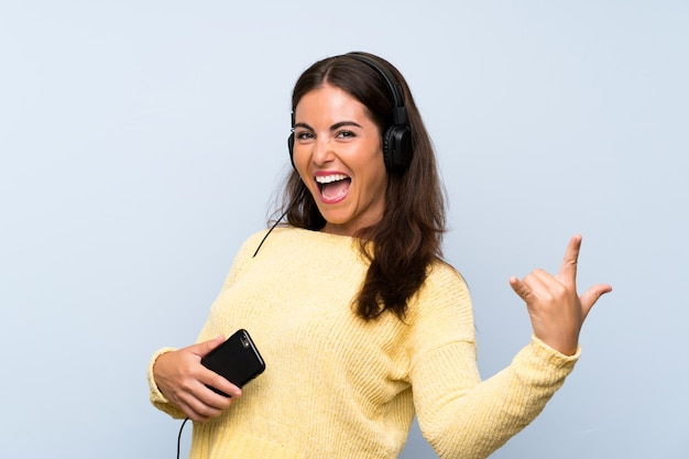 Young woman listening music with a mobile over isolated blue wall and dancing
