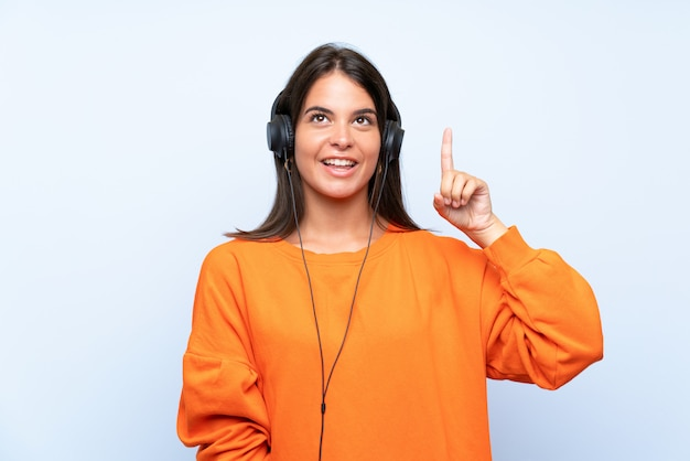 Young woman listening music with a mobile over isolated blue wall intending to realizes the solution while lifting a finger up