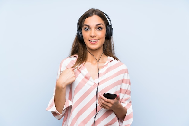 Young woman listening music with a mobile isolated blue wall with surprise facial expression