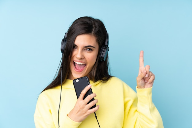 Young woman listening music with a mobile and singing