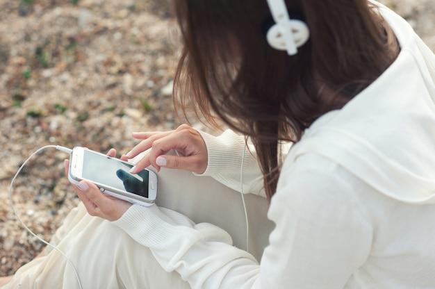 Музыка молодой женщины слушая с телефоном против морского песка.