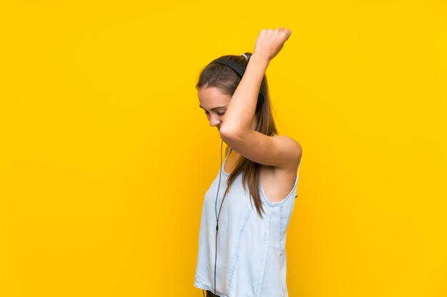 Young woman listening music  on yellow wall