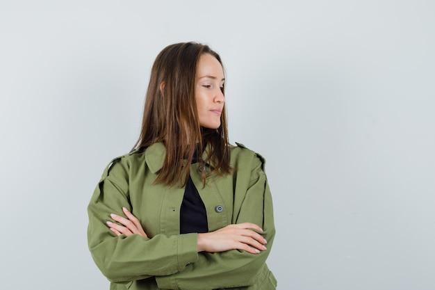 Giovane donna che ascolta qualcuno stando in piedi con le braccia incrociate in giacca verde e guardando attento, vista frontale.