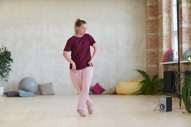 音楽を聴き、ダンススタジオでメロディーのビートに合わせてダンスを発明する若い女性
