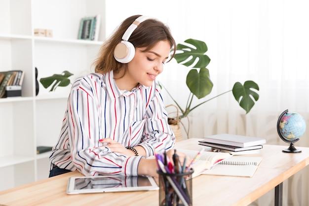 Молодая женщина слушает музыку и читает