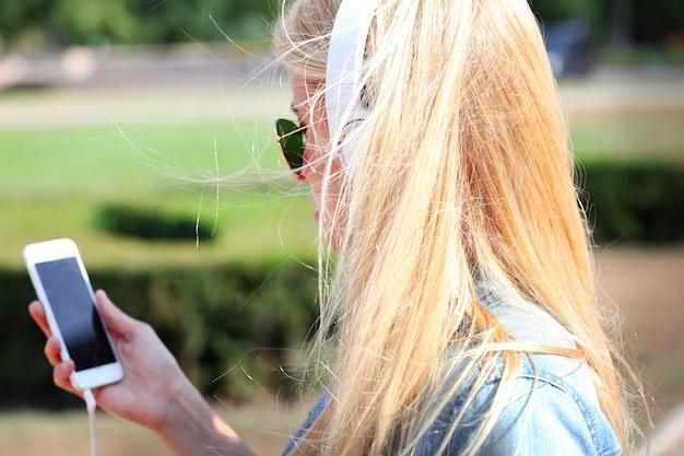 Молодая женщина слушает музыку и гуляет по улице