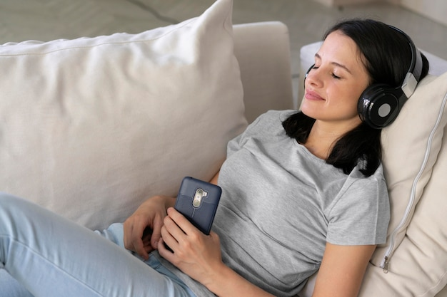 Молодая женщина, слушающая музыку дома