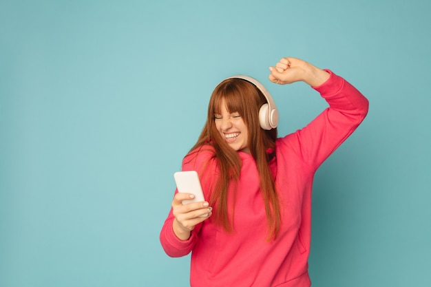 Молодая женщина, слушающая музыку, держа смартфон
