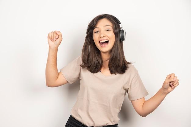 Молодая женщина, слушающая музыку в наушниках на белом фоне.