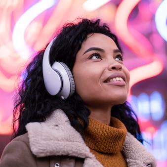 外のヘッドフォンで音楽を聴いている若い女性