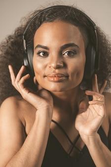 灰色の壁に分離された黒いトップを着てヘッドフォンで音楽を聴いて、感情的に動く若い女性