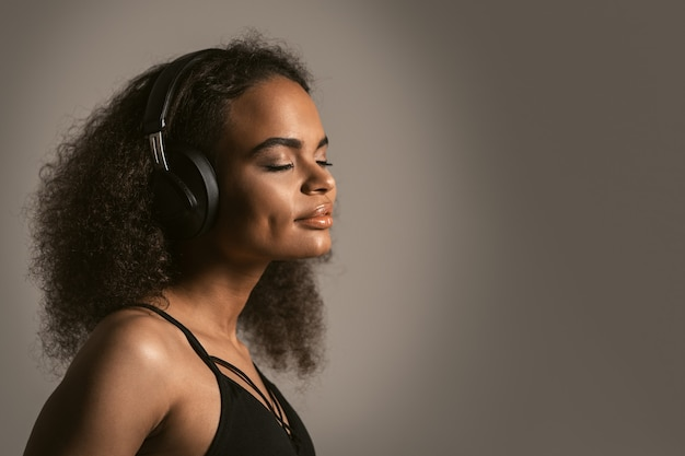 灰色の壁に分離された黒いトップを着てヘッドフォンで音楽を聴いている若い女性