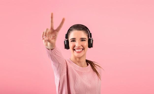 ピンクのポーズをとってピンクのセーターを着てワイヤレスヘッドフォンで音楽を聴いている若い女性