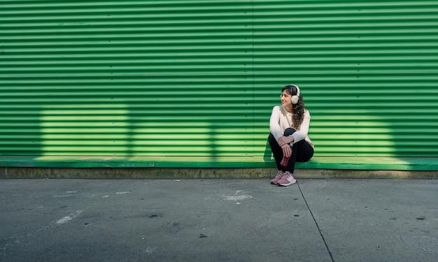 녹색 벽에 기대어 음악을 듣고 젊은 여자
