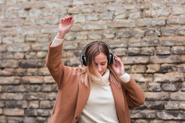 外のヘッドフォンで音楽を聴く若い女性