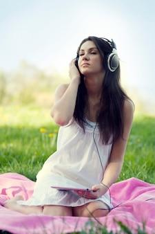 牧草地で音楽を聴いている若い女性