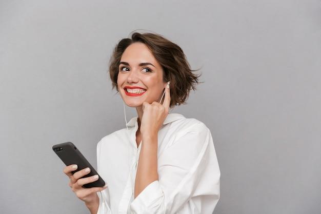 灰色の壁に隔離されたイヤホンを介してスマートフォンで音楽を聴いている若い女性