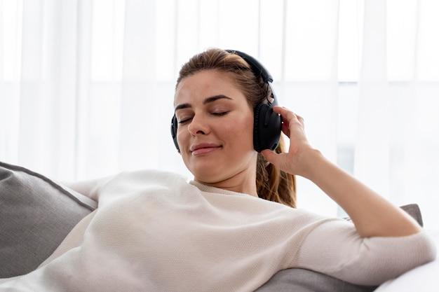 Молодая женщина слушает музыку через наушники