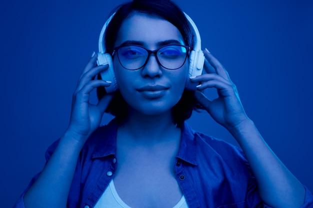 青い光の下で音楽を聴いている若い女性