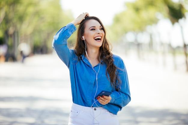 Молодая женщина слушает музыку через наушники на летней улице