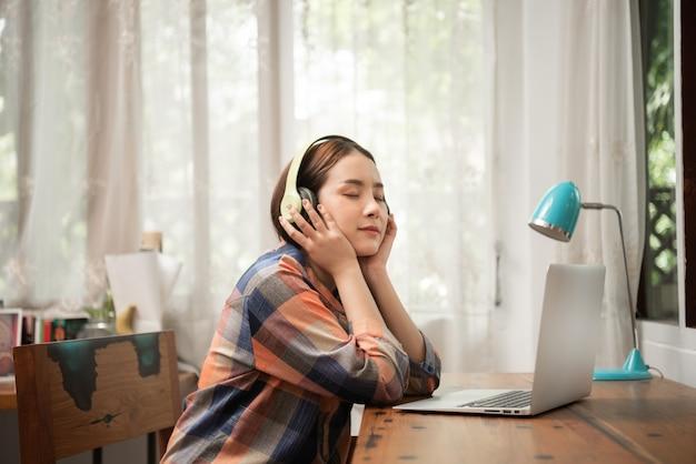 自宅でヘッドフォンで音楽を聴く若い女性