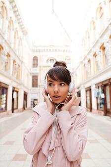 Молодая женщина слушает музыку в наушниках и смотрит на открытом воздухе