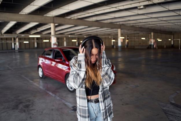 駐車場でヘッドフォンで音楽を聴いている若い女性。彼女はヘッドホンで音楽を聴いています。