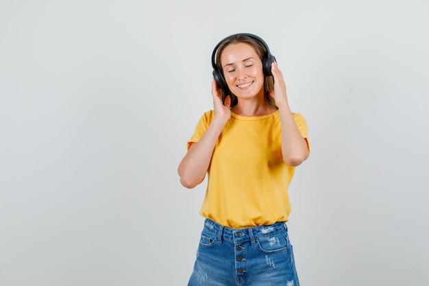 Tシャツ、ショートパンツ、リラックスしてヘッドフォンで音楽を聴いている若い女性。正面図。