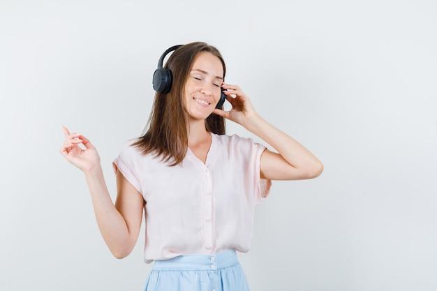 Молодая женщина слушает музыку с наушниками в футболке, юбке и выглядит расслабленной, вид спереди.