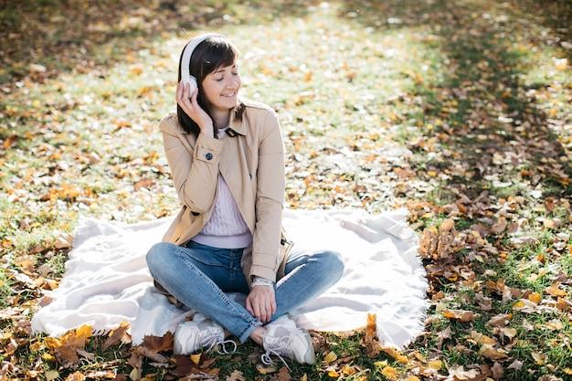 秋の森でヘッドフォンで音楽を聴く若い女性