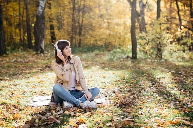 森の中でヘッドフォンで音楽を聴いている若い女性