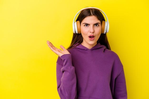 분홍색 벽에 고립 된 헤드폰으로 음악을 듣고 젊은 여자는 손바닥에 복사 공간을 잡고 감동