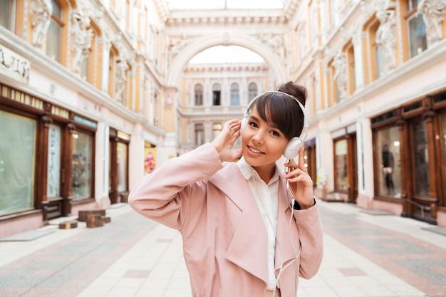 Молодая женщина слушает музыку в наушниках на улице города