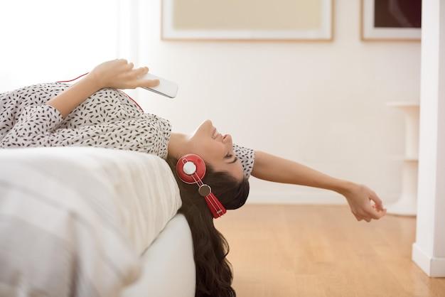ヘッドフォンで音楽を聴いている若い女性