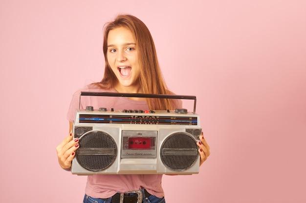 Молодая женщина слушает музыку с ретро кассетой радио