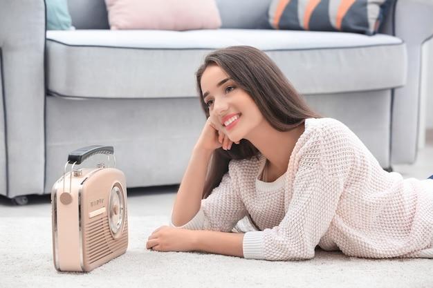 Молодая женщина слушает радио, лежа на ковре в комнате