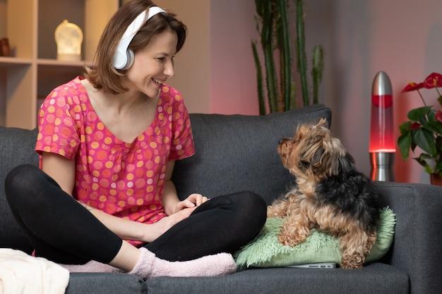若い女性がスマートフォンで音楽を聴いて、ソファに座ってリズムに移動します。