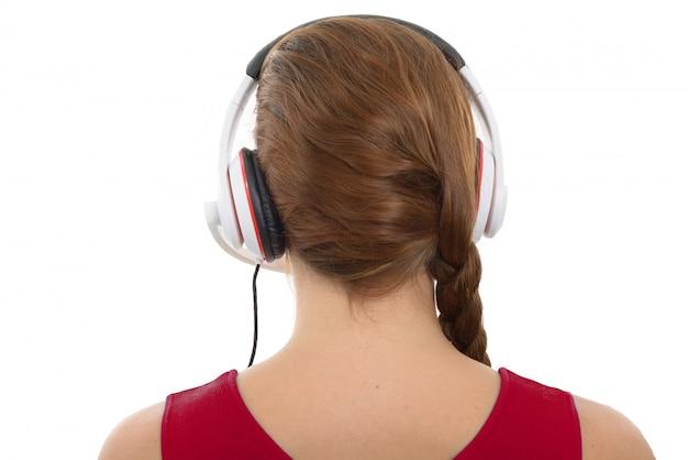 ヘッドフォン、背面図、白で音楽を聴く若い女性