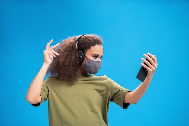 若い女性は、青い壁に隔離されたcovid-19感染から他の人を防ぐために、オリーブのtシャツ、再利用可能なフェイスマスクのヘッドフォンでスマートフォンで音楽を聴きます