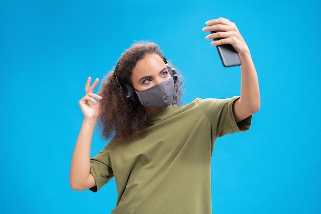 젊은 여성이 파란색 벽에 고립 된 covid-19 감염으로부터 다른 사람을 방지하기 위해 올리브 티셔츠, 재사용 가능한 안면 마스크의 헤드폰으로 스마트 폰에서 음악을 듣고 있습니다.