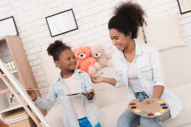 Young woman and little girl draw together.