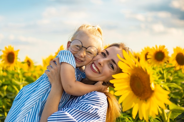 Young woman and a little girl in her arms on a sunflower field. mum with the child.