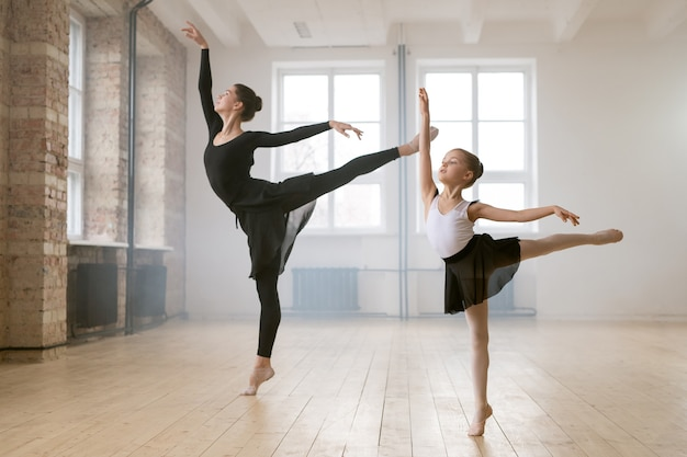 Young woman and little girl standing together in the same ballet pose and dancing in dance studio