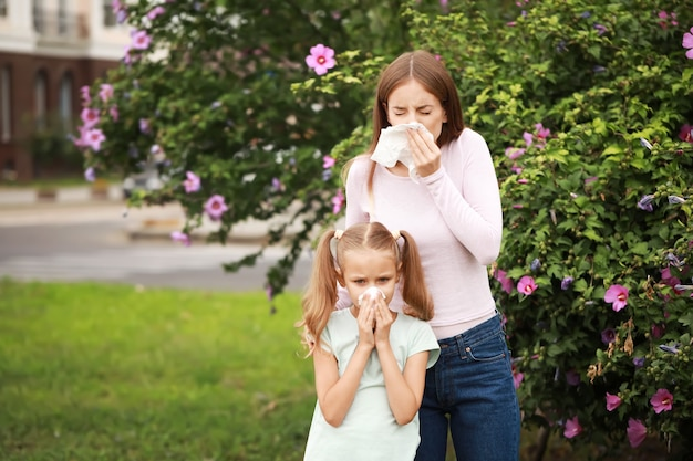 Young woman and little girl suffering from allergy outdoors