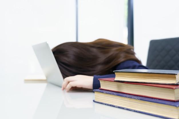 若い女性の長い髪のラップトップを机の上で眠りに落ちる