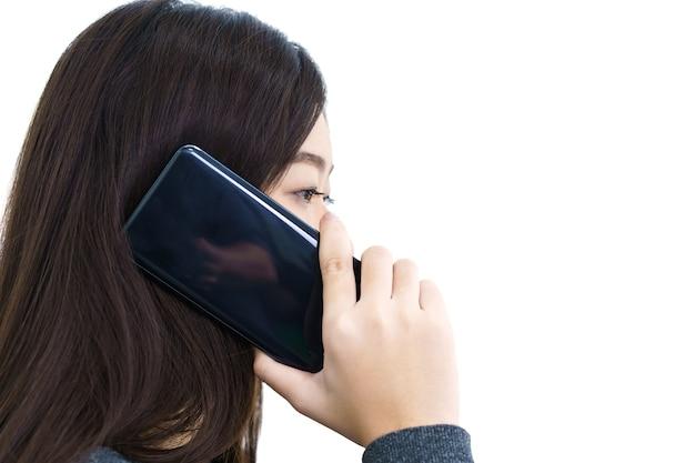 白い背景の上の携帯電話で話している若い女性の長い髪