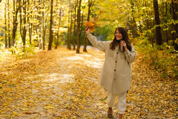 A young woman in a long shirt with a thermo mug in her hands walks through the autumn forest