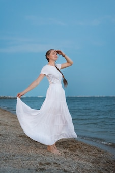 Young woman in long white dress stands on shore of sea background.
